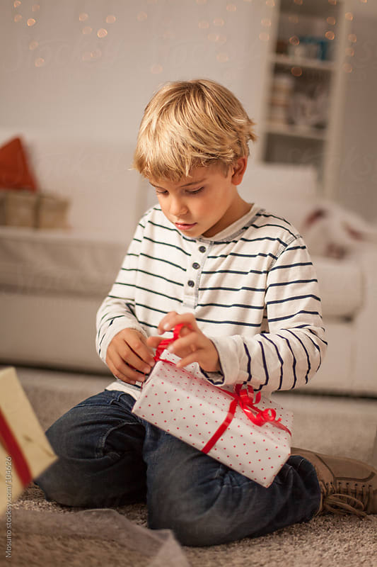 Cute Boy Opening Christmas Gift at Home by Mosuno for Stocksy United