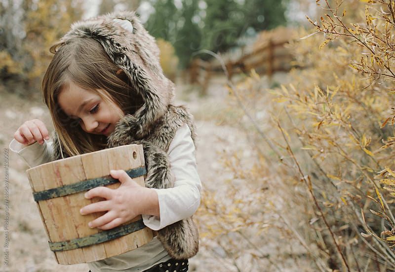 toddler girl holding bucket collecting leaves by Kristin Rogers Photography for Stocksy United