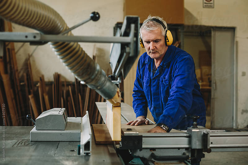 woodworker with yellow protection earmuffs working on a bench saw