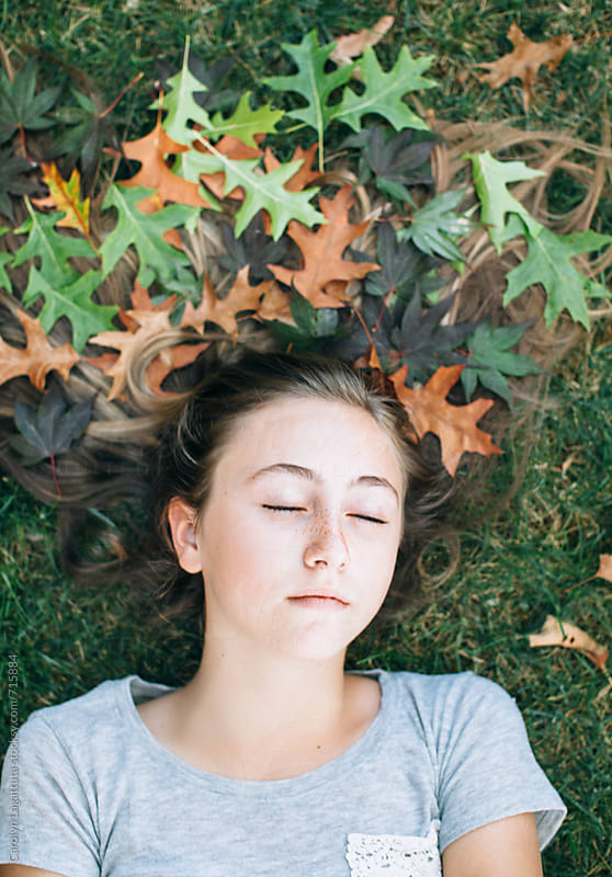 Teenage girl laying in the grass with her long hair decorated with fallen leaves by Carolyn Lagattuta for Stocksy United