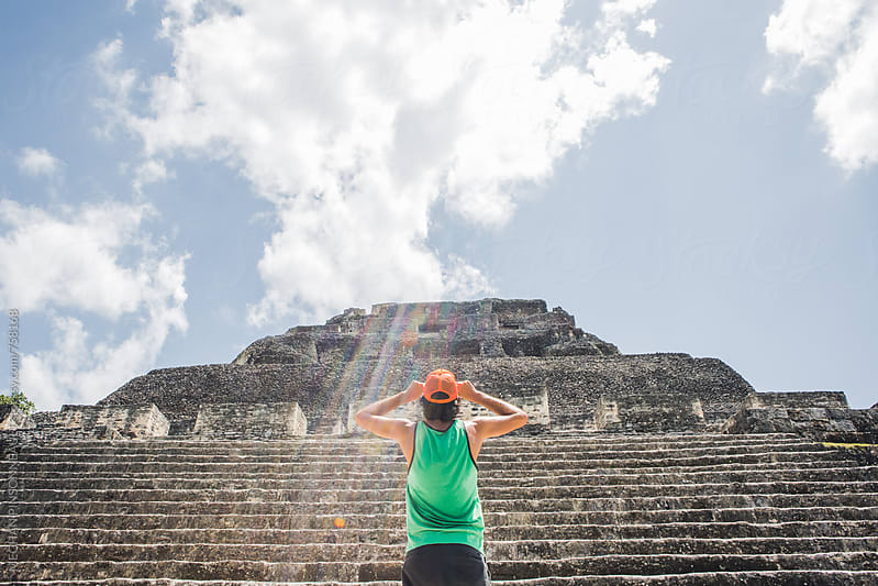 Man Holds His Hat While Looking Up at Ancient Mayan Temple by Meg Pinsonneault for Stocksy United