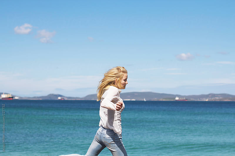 Carefree teen girl jumping across rocks on the foreshore by Jacqui Miller for Stocksy United