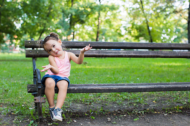 Funny Little Girl Sitting in the Park by Mosuno for Stocksy United