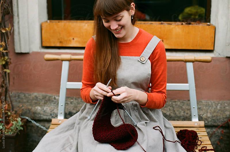 Young woman knitting outdoors  by Liubov Burakova for Stocksy United