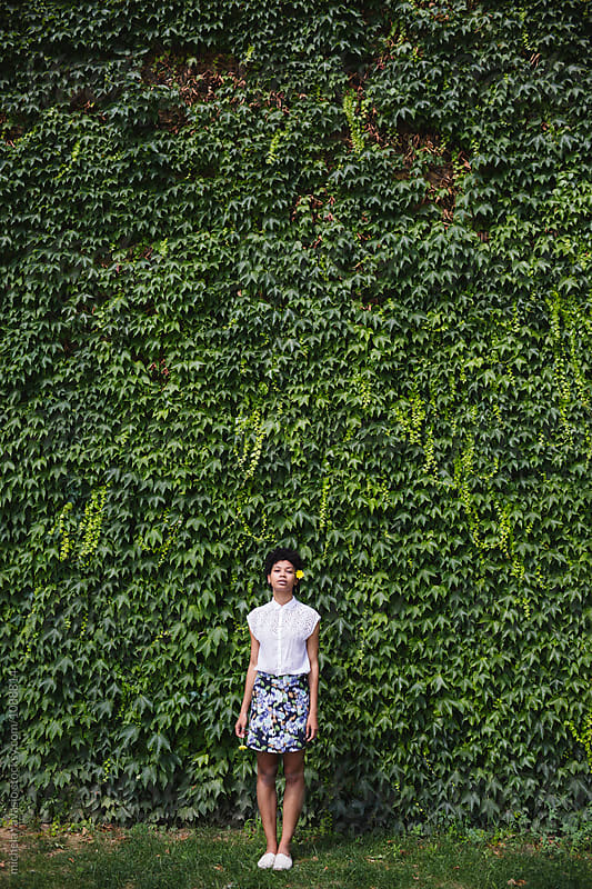 Girl standing in front of a wall covered with ivy by michela ravasio for Stocksy United