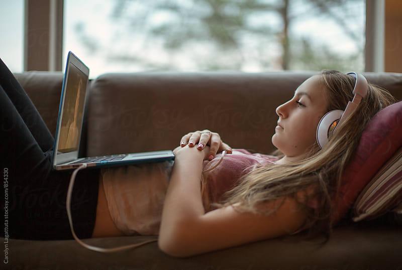 Teenage girl watching TV on her laptop by Carolyn Lagattuta for Stocksy United