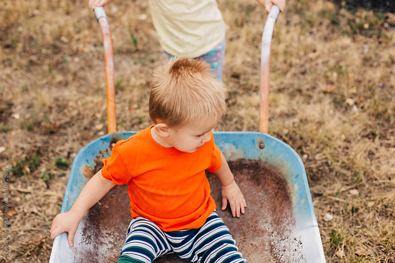 Young toddler boy sitting in a wheelbarrow that is being pushed by his sister. by Jessica Byrum for Stocksy United
