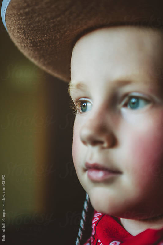 Young boy dressed up like a cowboy with hat and bandana by Rob and Julia Campbell for Stocksy United