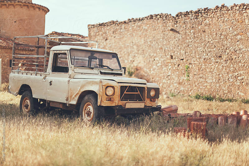 abandoned car in a small town by Javier Pardina for Stocksy United