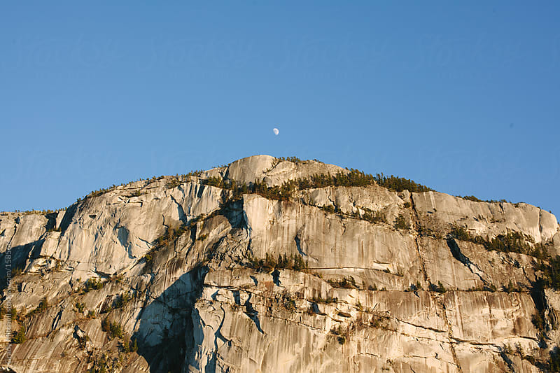 Moon Rests Over A Mountain Face by Grady Mitchell for Stocksy United