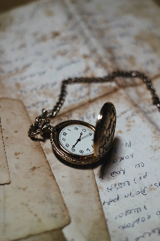 Old watch on an old letters and photographs by Jovana Rikalo for Stocksy United