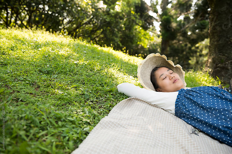 Woman lying on picnic blanket on green grass at park by Lawren Lu for Stocksy United