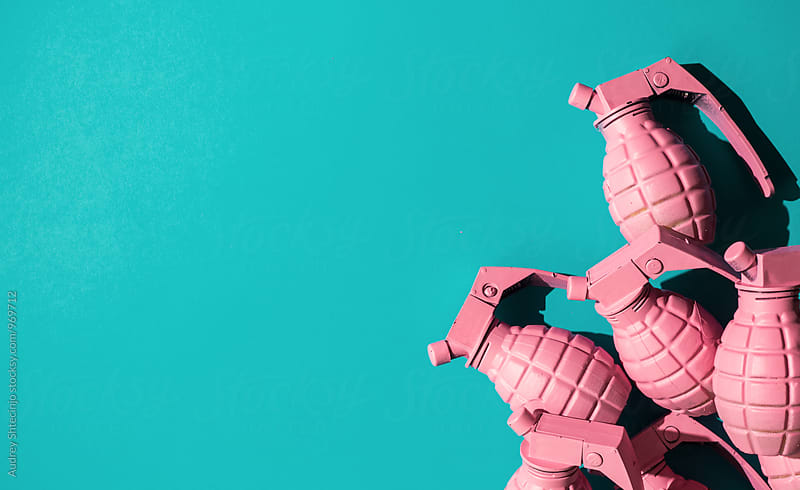 Pink hand grenades on blue background. by Audrey Shtecinjo for Stocksy United
