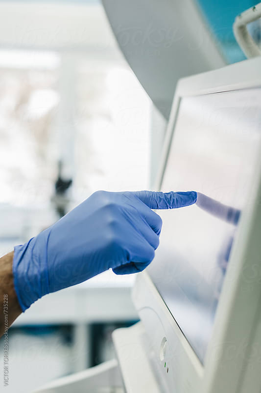 Biologist Using a Touch Screen Display Unit in a Laboratory by VICTOR TORRES for Stocksy United