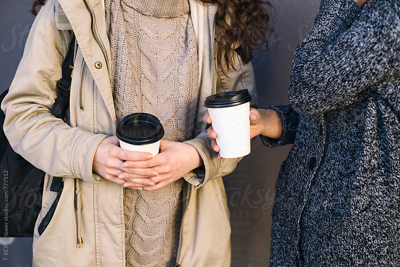 Two young women holding coffee to go by Danil Nevsky for Stocksy United