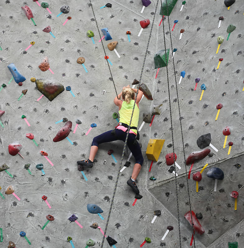 Girl climbing to the top of the rock wall by Carolyn Lagattuta for Stocksy United