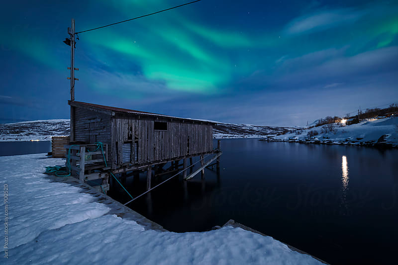 a cabin under northern lights by Juri Pozzi for Stocksy United