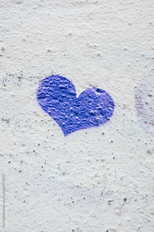 Small heart shape spray painted onto building wall, close up by Paul Edmondson for Stocksy United