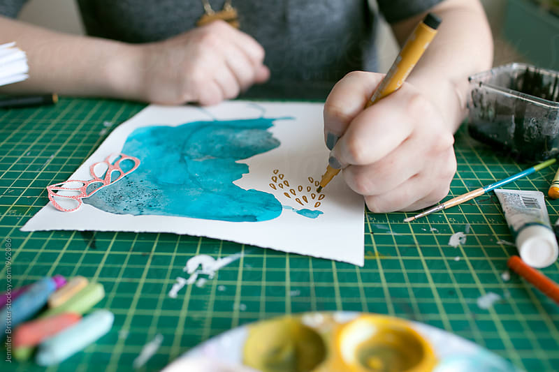 Artist creating colorful art on messy table  by Jen Brister for Stocksy United
