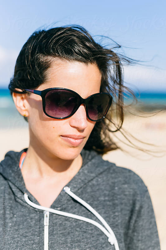 Casual woman portrait in a windy beach, wearing sunglasses and a grey hoodie by Inuk Studio for Stocksy United