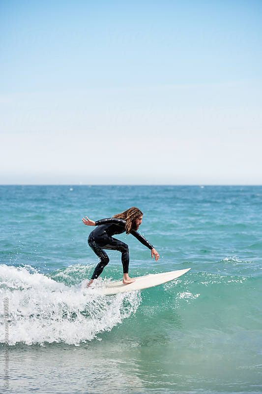 Side view of surfer riding waves by Guille Faingold for Stocksy United