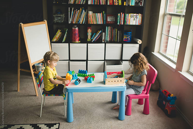 Siblings playing at homeschool table by Courtney Rust for Stocksy United