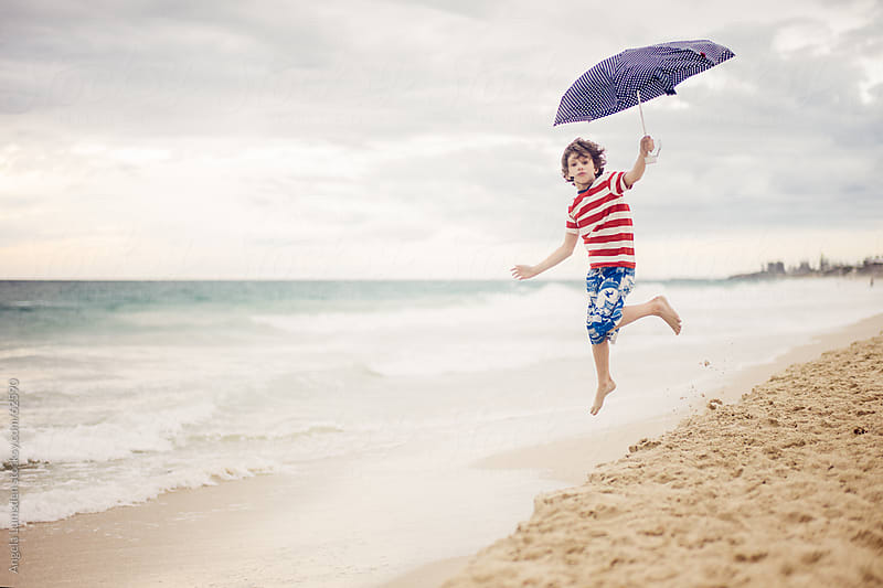 Boy trying to fly with an umbrella at the beach by Angela Lumsden for Stocksy United