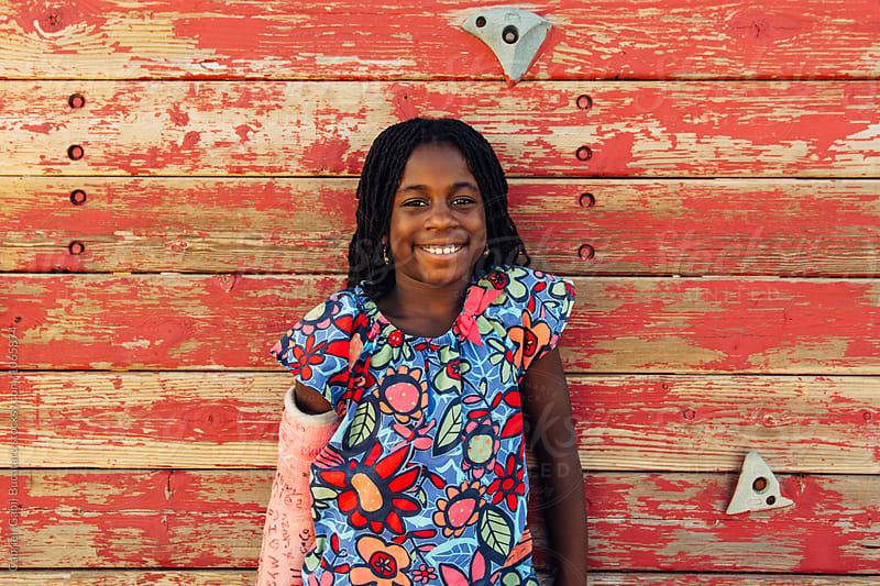 Smiling African American girl with a cast by a climbing wall by Gabriel (Gabi) Bucataru for Stocksy United