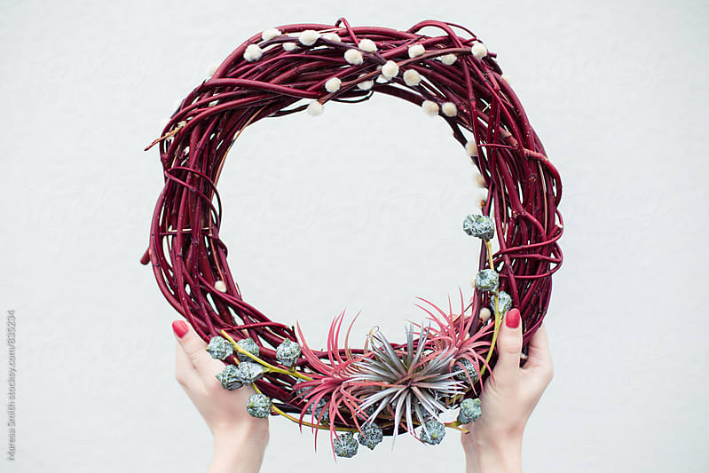 Hands holding a red wood wreath against a white wall by Maresa Smith for Stocksy United