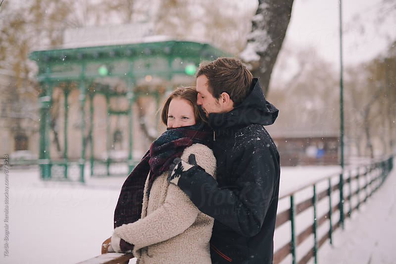 Lovely young couple in the snowfall by Török-Bognár Renáta for Stocksy United