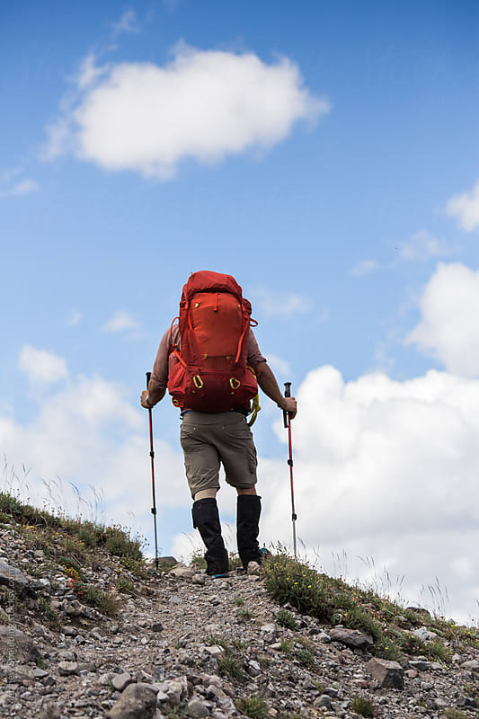 Hiker backpacking and exploring remote alpine wilderness area on trail by Matthew Spaulding for Stocksy United