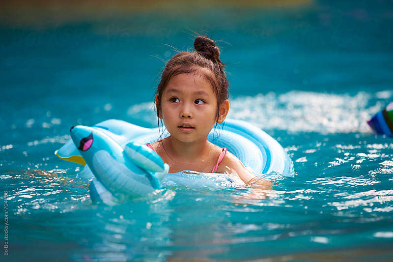 happy little asian girl in swimmnig pool by Bo Bo for Stocksy United