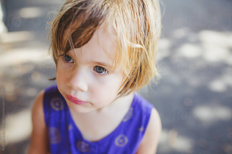 Cute 4 year old girl with wet hair and purple romper - blank stare by Rob and Julia Campbell for Stocksy United