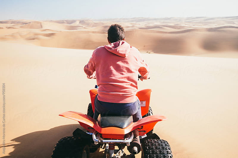 Back view of man on quad bike by Alejandro Moreno de Carlos for Stocksy United