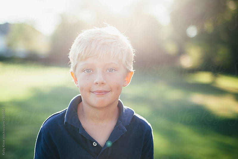 outdoor portrait of a happy boy in afternoon light by Kelly Knox for Stocksy United