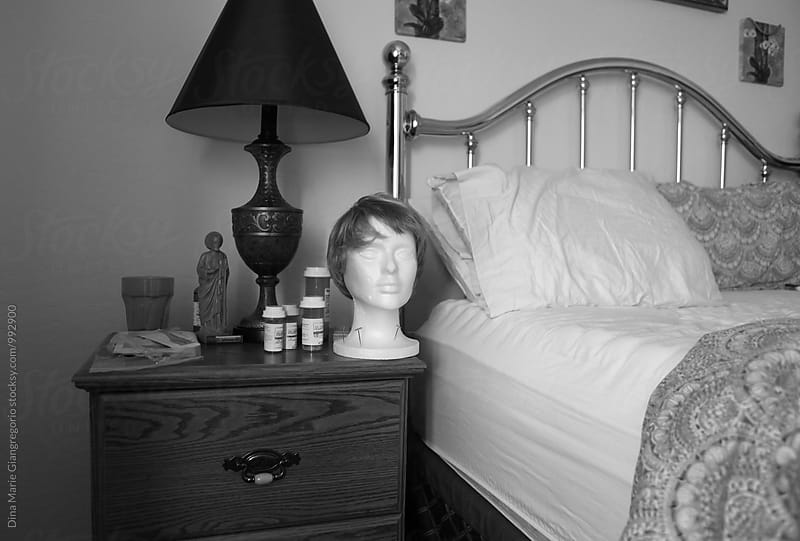 Bed and Nightstand With Wig Holder, Medications and Religious Statue by Dina Giangregorio for Stocksy United
