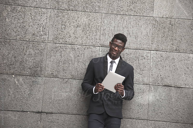 African young businessman standing on a wall with a tablet by BONNINSTUDIO for Stocksy United