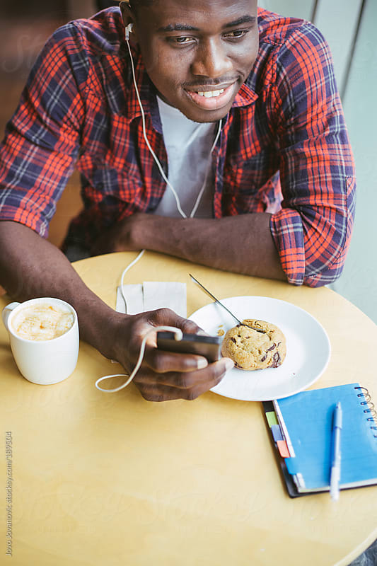 Student checking his smartphone and enjoying his time at university cafeteria by Jovo Jovanovic for Stocksy United