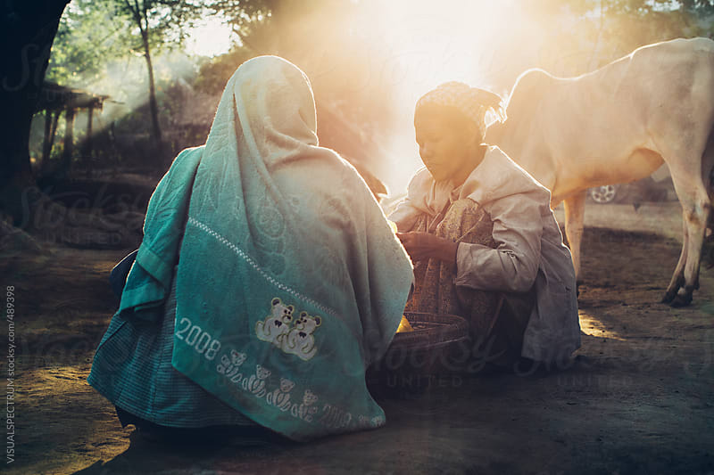 Two Burmese Women Trading Goods in Early Morning Sunlight by VISUALSPECTRUM for Stocksy United
