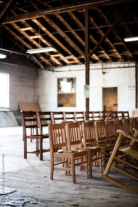 Chairs lined up in rows in a warehouse workshop by J Danielle Wehunt for Stocksy United