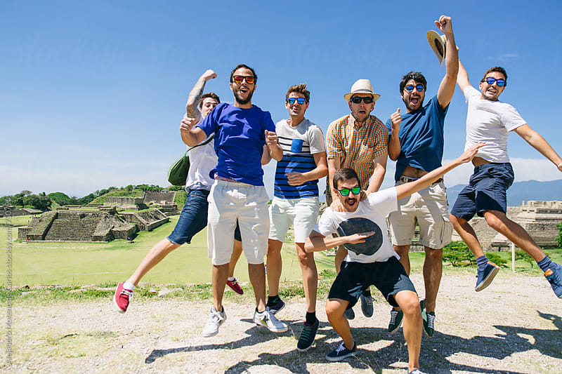 Group of happy friends jumping excited in a touristic landmark of ancient ruins by Alejandro Moreno de Carlos for Stocksy United