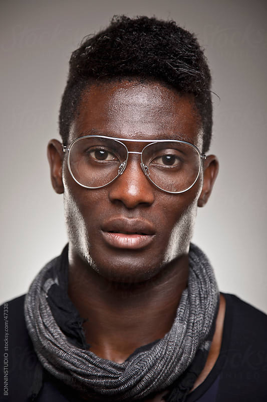 A real african man with retro glasses over grey background by BONNINSTUDIO for Stocksy United