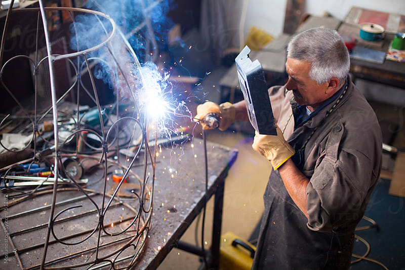 Old craftsman welding in his workshop. by Mosuno for Stocksy United