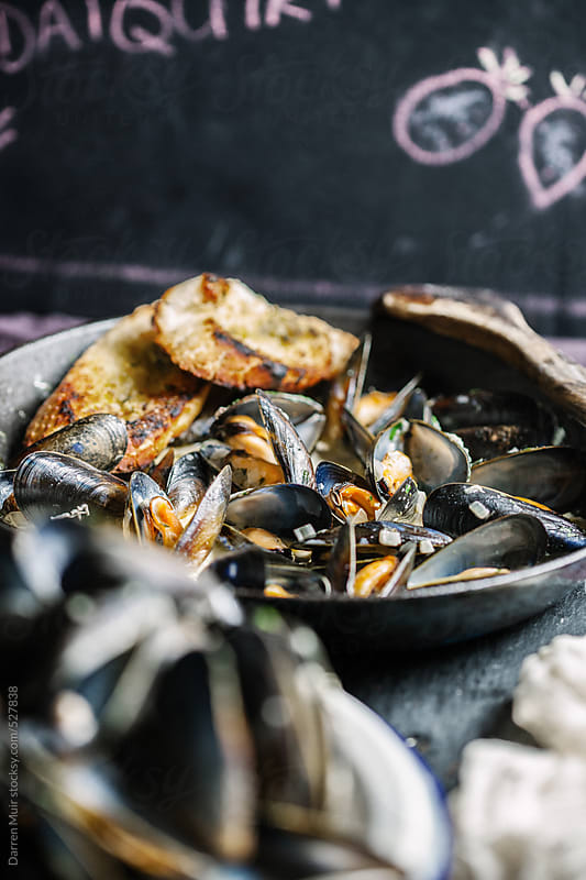 Cooked mussels in cast iron pan on table. by Darren Muir for Stocksy United