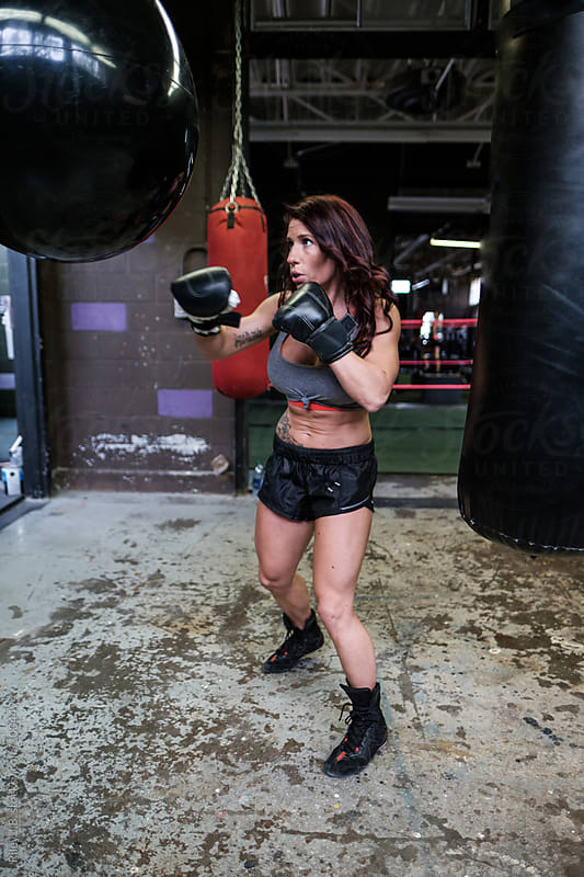 A muscular woman boxing in a gritty gym by Riley J.B. for Stocksy United