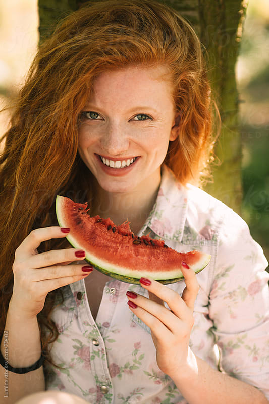 Smiling Woman Eating Watermelon by Lumina for Stocksy United