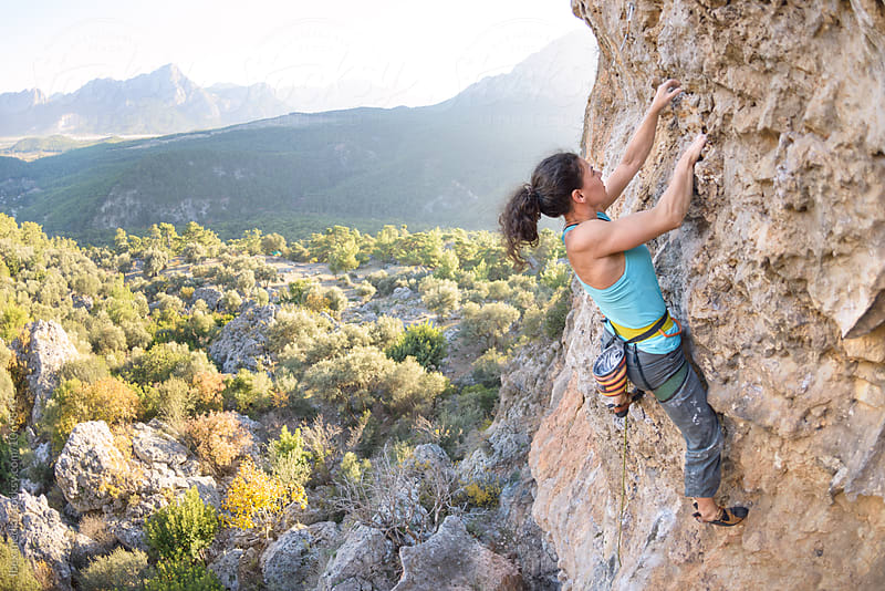 Woman climbing a steep rock wall outdoor by RG&B Images for Stocksy United