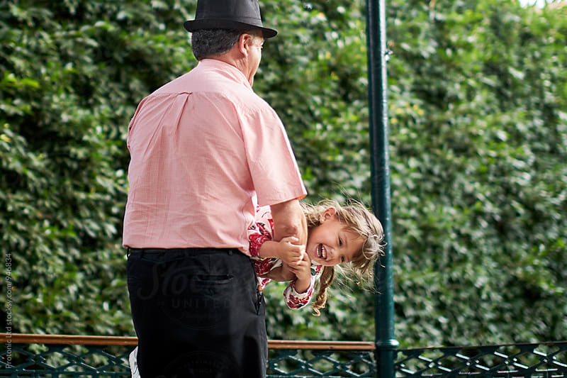 Grandfather  playing with happy granddaughter by Per Swantesson for Stocksy United