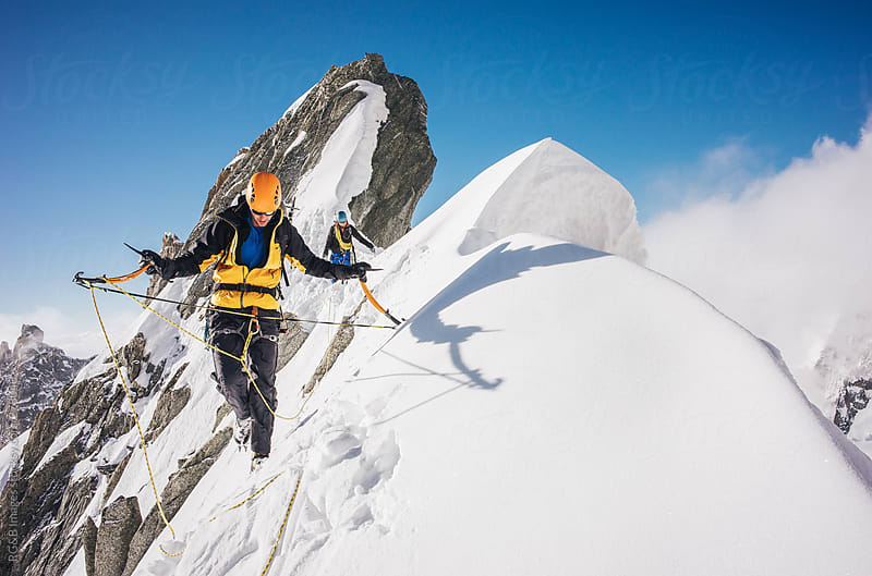 Crossing a steep snowy ridge  by RG&B Images for Stocksy United
