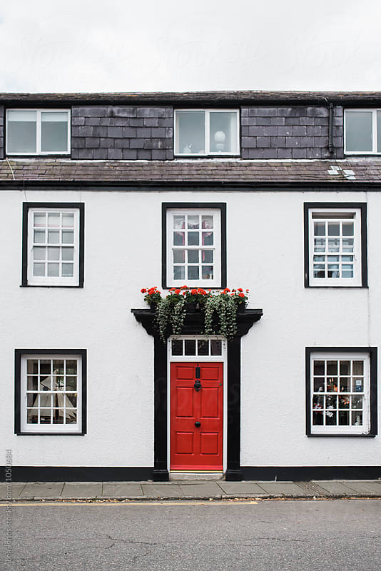 white house with red door by Léa Jones for Stocksy United